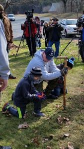 A disabled Veteran kneels in Prayer at the location of a removed Monument. His Grandsons flank his sides. Click to enlarge.
